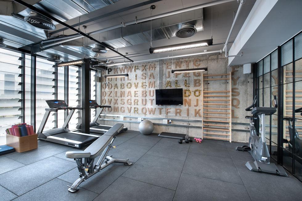 בצדה השני של הקומה חדר כושר, עם קיר בטון שעליו בולטות אותיות עץ לועזיות (צילום: עמית גושר)