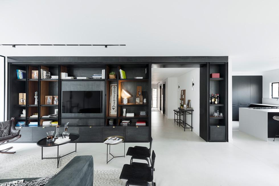 ספריית ברזל שחורה מגדירה את הסלון ומטשטשת את נוכחותו של מסך הטלוויזיה. היא עוטפת כמשקוף את המבואה והמעבר אל חדרי השינה. המסדרון הורחב ל-130 סנטימטרים, נבנה בו ארון גדול ובסופו מאיר חלון שהוגדל (צילום: גדעון לוין)