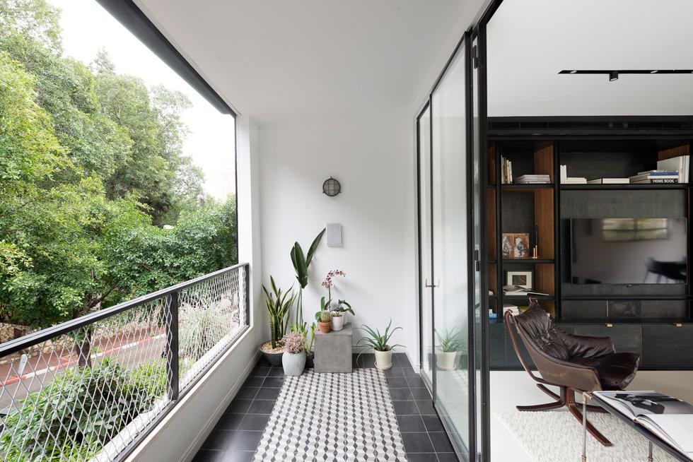 המרפסת מקורה, אך נפרדת מהסלון. על הרצפה אריחי בטון מצוירים בגוני אפור-שחור-לבן (צילום: גדעון לוין)