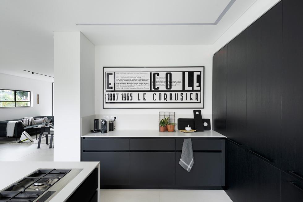 המטבח פתוח חלקית אל הסלון, ובולטת בו עבודה גרפית של אתי אלימלך, שהייתה תלויה קודם בחדר השינה של אבקסיס, ואסבן שיכנע אותו שתתאים היטב למטבח (צילום: גדעון לוין)