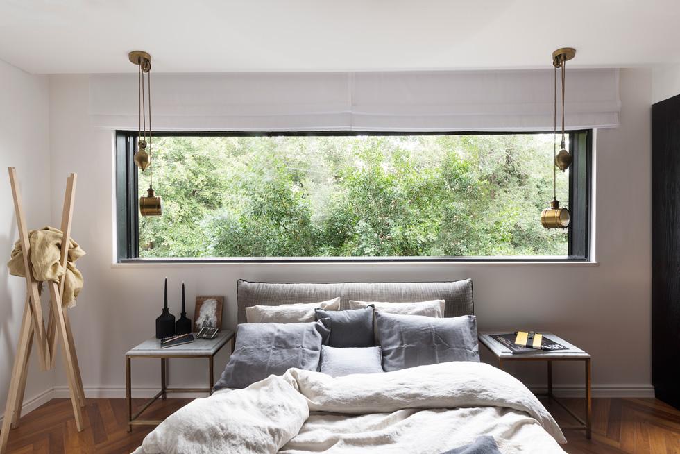 המיטה המרופדת הוזמנה במיוחד, מנורות הצד נתלו מהתקרה ולרוחב הקיר נפתח חלון גדול, ששוטף את החדר באור (צילום: גדעון לוין)