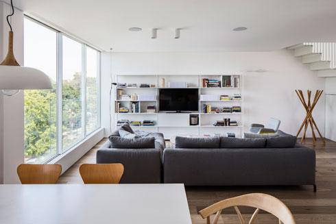 מבט מהמטבח אל הסלון. ספריית המתכת לבנה כמו הקיר, וכמו גרם המדרגות (צילום: עמית גרון)