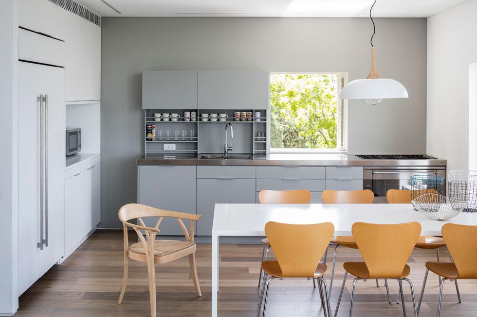 המטבח עוצב בפשטות ובאלגנטיות: ארונות תחתונים אפורים על רקע קיר בגוון זהה, ומשטח נירוסטה. המקרר מוסווה בקיר ארונות גבוהים ולבנים (צילום: עמית גרון)