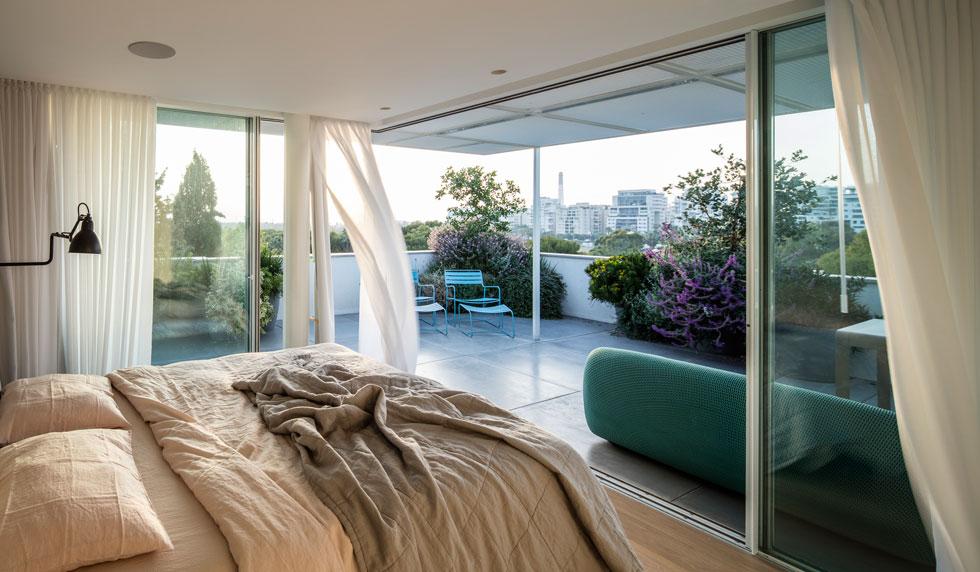 חדר השינה פונה למרפסת גג רחבה. פרגולת מתכת לבנה מייצרת המשכיות נעימה של מישור התקרה החוצה (צילום: עמית גרון)