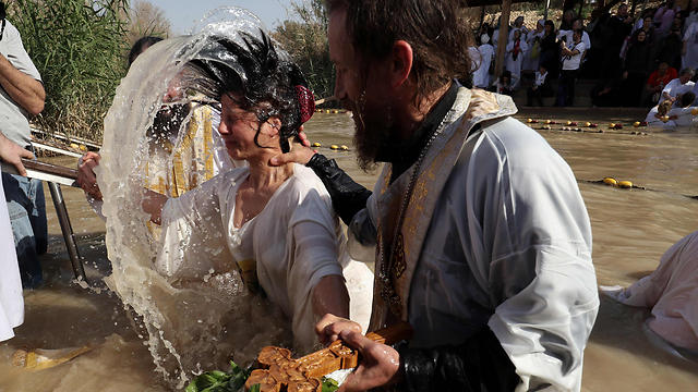 Romanian priest baptizing a pilgrim (Photo: AFP) (Photo: AFP)