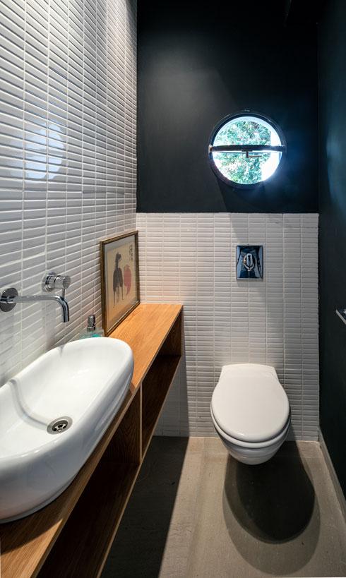 חדרי השירותים חופו בקרמיקה לבנה. צבע מוסיף להם עניין. לשירותי ההורים והאורחים נבחר כחול כהה. בשירותי הילדים - צהוב (צילום: עוזי פורת)