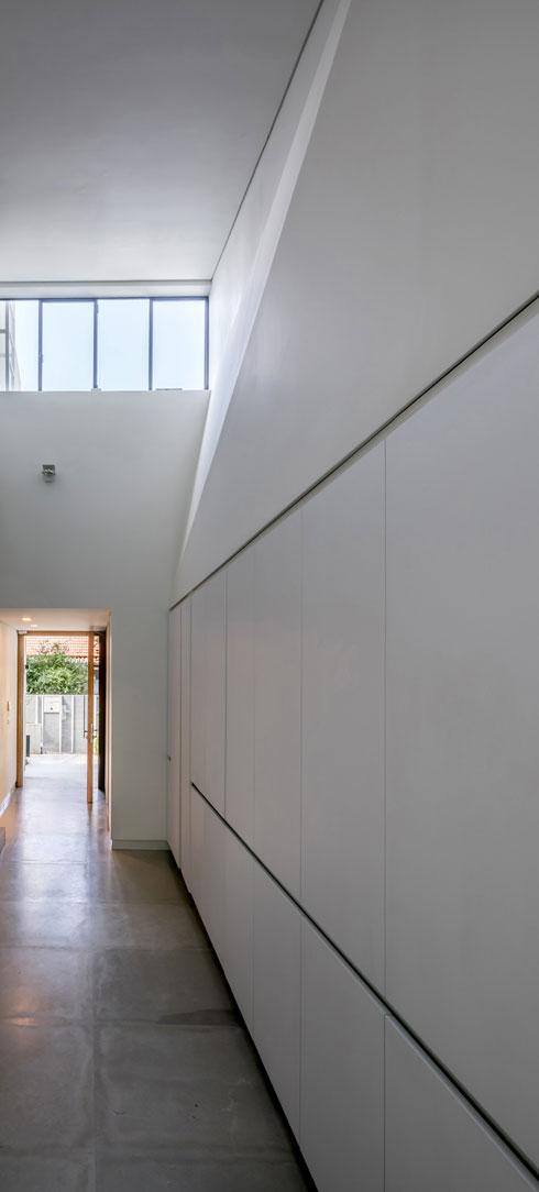 חלונות הסרט מעל דלת הכניסה. ריצוף  האבן האפורה נמשך מהחצר הקדמית אל תוך הבית (צילום: עוזי פורת)