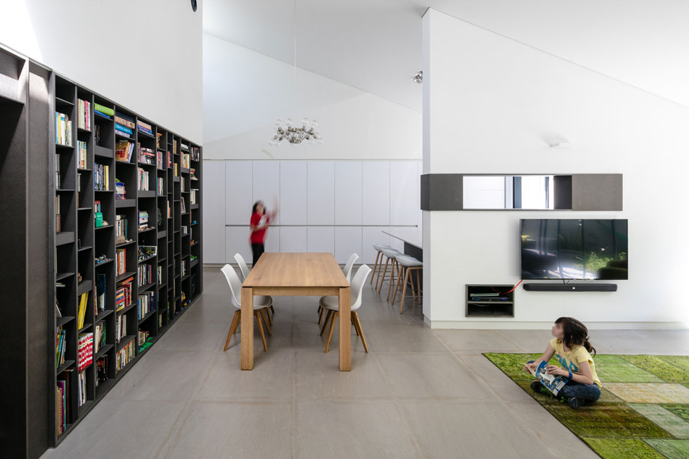 ספרייה גדולה נבנתה על הקיר שמפריד בין הסלון לאגף הילדים. ארון נוח תוכנן על הקיר שמחבר בין המטבח לדלת הכניסה (צילום: עוזי פורת)