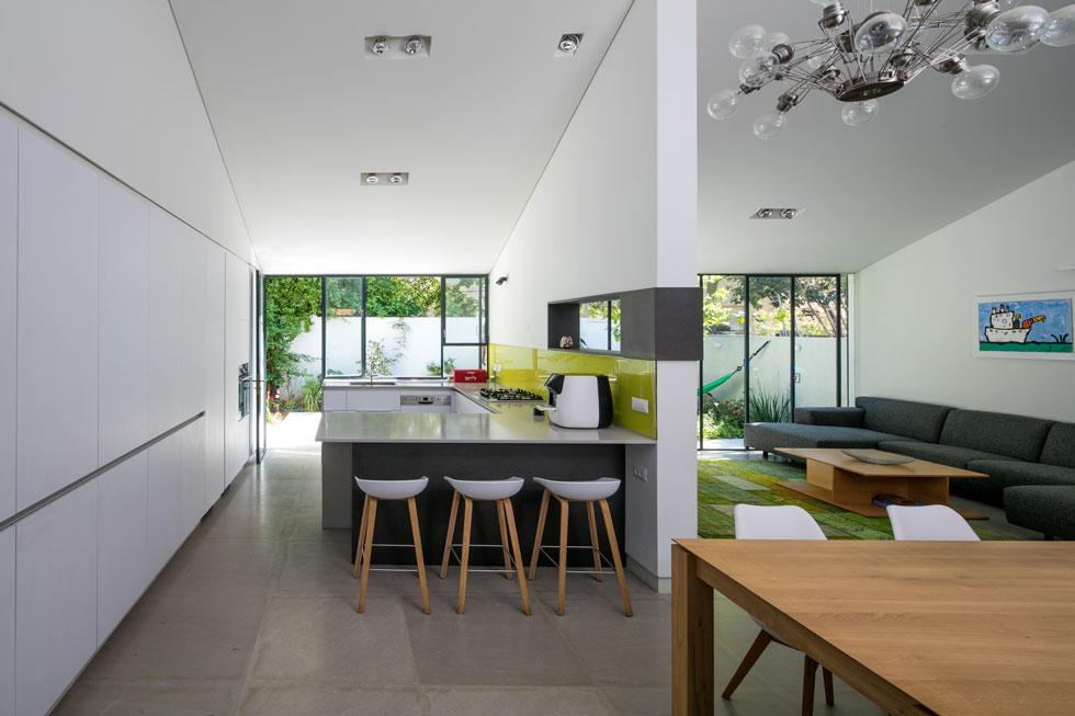 הסלון והמטבח פונים אל החצר האחורית, וביניהם מפריד קיר תומך. האדריכלים פערו בו פתח מלבני, שמאפשר קשר עין בין שני החללים (צילום: עוזי פורת)