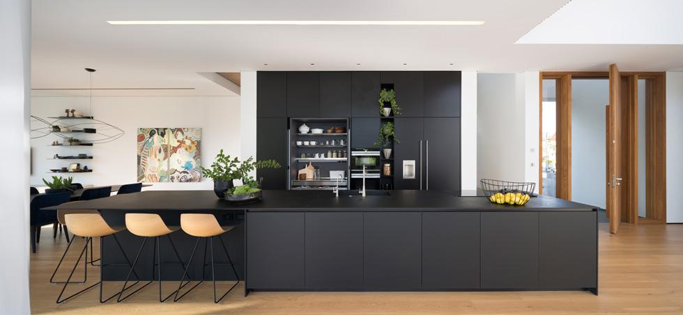 המטבח מוקם בין הדלת לסלון, וכולו שחור. מול חזית של ארונות גבוהים נבנה אי באורך 6 מטרים, שמשמש גם כמשטח עבודה וגם לישיבה ואכילה (צילום: שי אפשטיין)