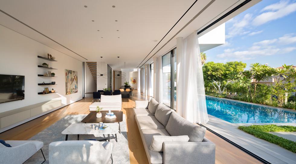 הסלון עוצב בצבעים בהירים, עם שידה תלויה ומדפים מינימליסטיים על הקיר (צילום: שי אפשטיין)