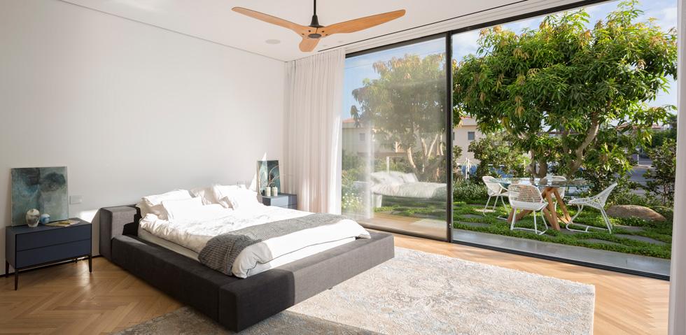 המיטה פונה כלפי חוץ והפרקט מוביל כשביל אל שני החלקים האחרים של היחידה - חדר הארונות וחדר הרחצה (צילום: שי אפשטיין)