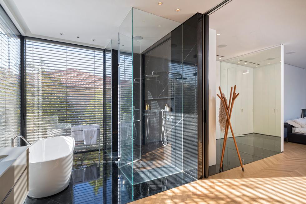 בתווך חדר הלבשה תחום בארונות לבנים וקיר מראה, ובחדר הרחצה קירות זכוכית, עם תריסים חיצוניים. הצמחייה בחצר מסייעת ליצור אינטימיות (צילום: שי אפשטיין)