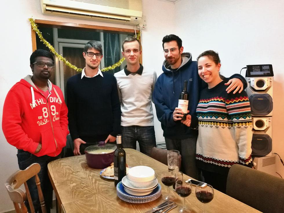 """שיר אוחנונה ועמנואל אברהמי (מימין) עם הסטודנטים הזרים בביתם בבאר שבע. עד כה התקיימו עשר ארוחות בהשתתפות כ-30 אורחים מחו""""ל  (צילום: סהר אלמוג)"""