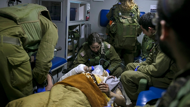 IDF medical personnel treat a wounded Syrian in an ambulance on the Israel-Syria border (Photo: Reuters)
