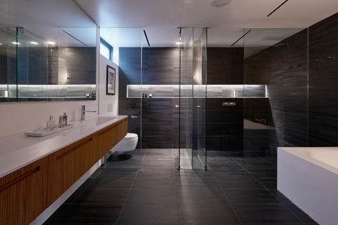 חדר רחצה דרמטי עם אריחי פורצלן שחורים, מחיצות שקופות ותאורה שקועה (צילום: Bruce Damonte)