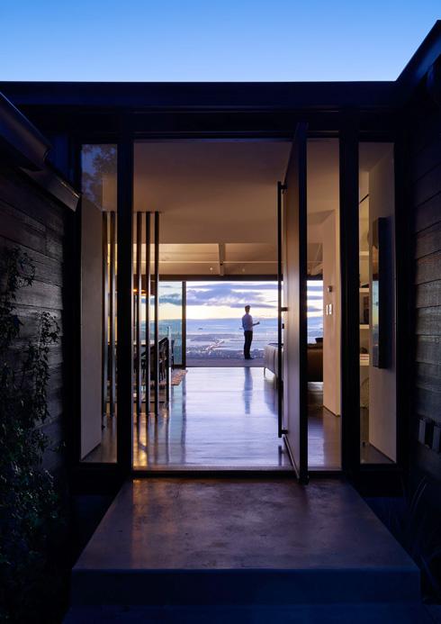 קורות העץ נצבעו באפור, דלת הכניסה עשויה ברזל שחור ומסתובבת לפתיחה אנכית שלמה (צילום: Bruce Damonte)
