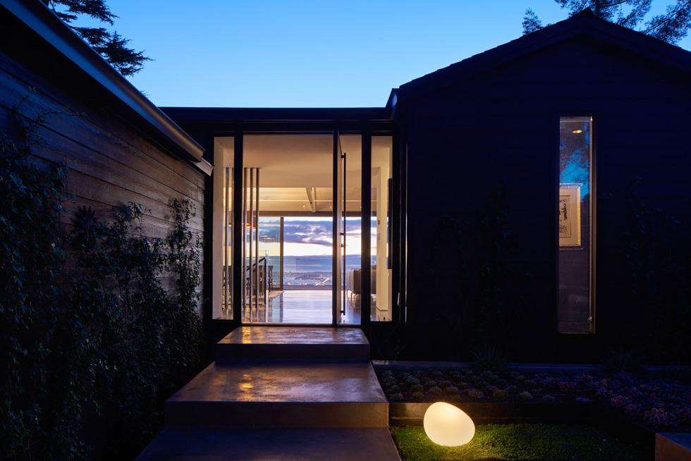 הבית נבנה ב-1939 כבית עץ קליפורני טיפוסי, ונקנה בידי רופא שינים חובב עיצוב. גם לאחר השיפוץ קווי המתאר של הבית נשארו כשהיו, וההתערבות נעשתה בתוכם. קומת הכניסה היא קומת הסלון והמטבח, ולמטה, במורד המצוק, יש קומת חדרי שינה, פרטית ואינטימית יותר (צילום: Bruce Damonte)