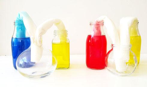 מכניסים צד אחד של גליל הנייר לבקבוק המלא ואת הצד האחר לבקבוק הריק (צילום: שירה פורר)