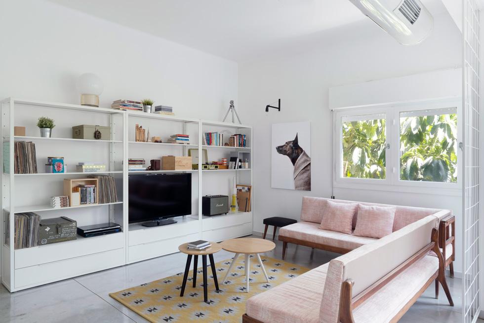 בסלון ספה פינתית שהייתה בדירה הישנה, ורופדה מחדש בבד ורוד. הרצפה כוסתה בבטון מוחלק (צילום: גדעון לוין)