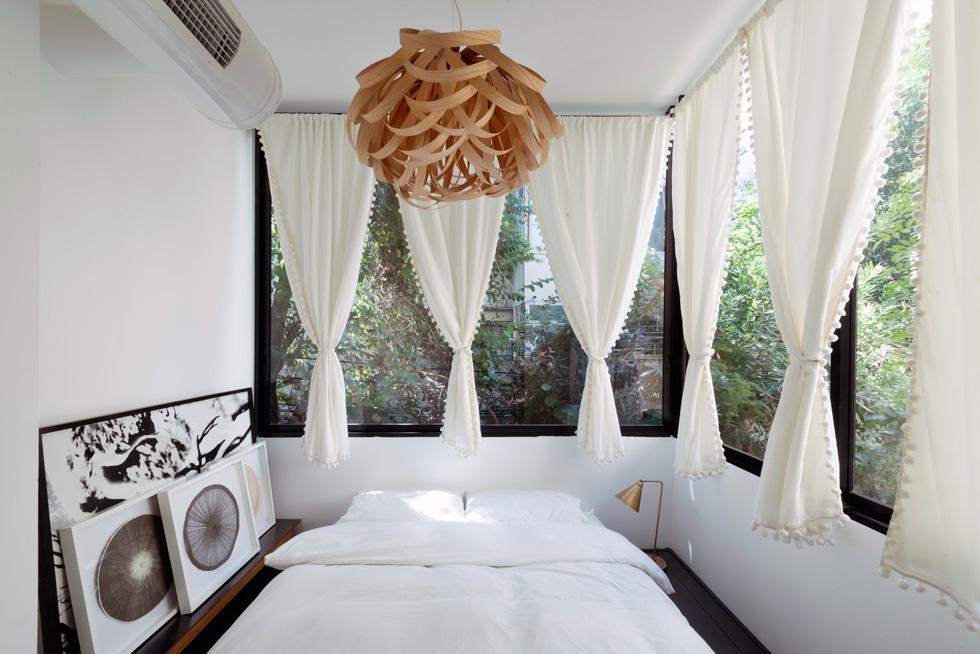 חדר ההורים מחולק לשלושה, והמיטה נמצאת בחלל קטן שקודם לשיפוץ היה מרפסת סגורה (צילום: גדעון לוין)