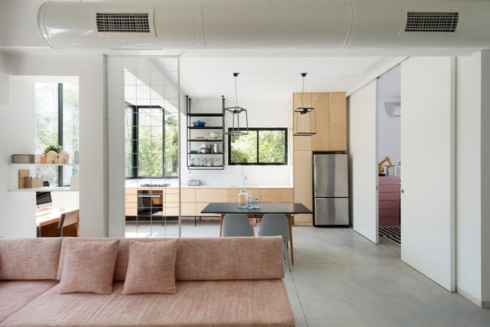 חציצה חלקית בין הסלון למטבח מייצרים עמוד תומך, רשת ברזל שעליה ייתלו עציצים ושני מדפים לבנים. לצד המטבח תוכנן חדר משחקים, עם דלתות הזזה גדולות (צילום: גדעון לוין)