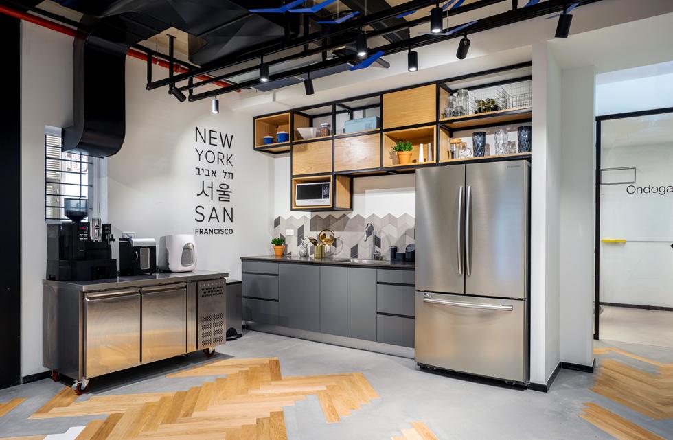 גם בפינת המטבח מופיעה דוגמת אדרת הדג, המאפיינת את כל המשרדים. המוטיב משתלב בבטון המוחלק עד שהוא ''משתלט'' עליו, ככל שמתקרבים למרכז הקומה (צילום: יואב פלד)