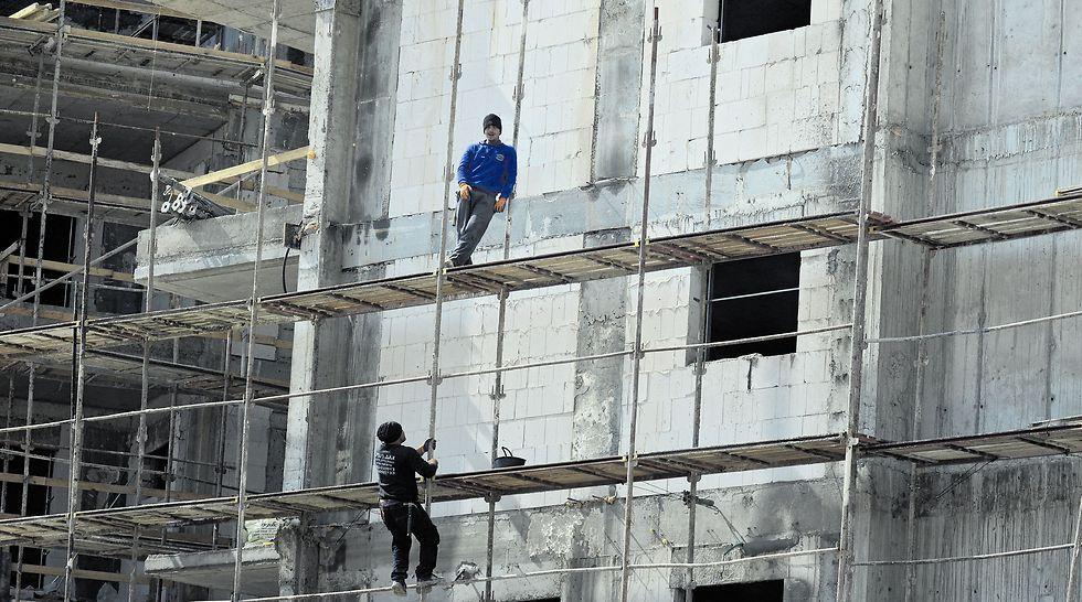 """עובדים באתר בנייה. """"מטפסים גבוה בלי קסדות""""  (צילום: הרצל יוסף)"""