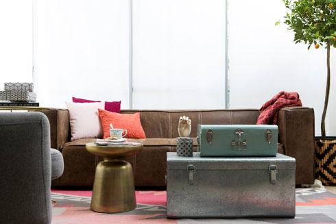 הסלון. שולחן צד רוסס בספריי זהב, הכריות והשטיח מוסיפים ורוד-כתום-אדום (צילום: שירן כרמל)