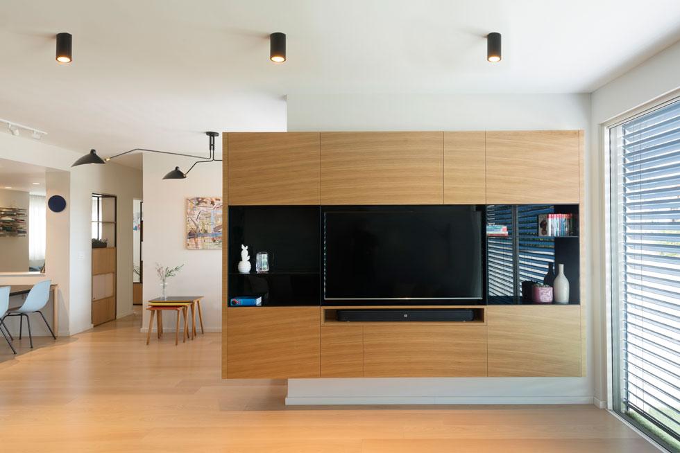 קופסת העץ מנותקת מהרצפה ומהתקרה, וזכוכית שחורה סוגרת על המדפים ומטשטשת את נוכחותו של מסך הטלוויזיה (צילום: גדעון לוין)