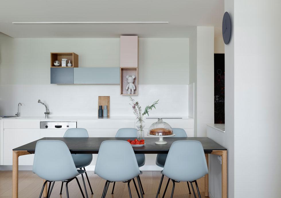 במטבח הלבן לא נעשו שינויים, מלבד החלפה של ארון הקאפה העליון ביחידה של קוביות בצבעים רכים, שתואמים גם את כיסאות האוכל שנבחרו (צילום: גדעון לוין)