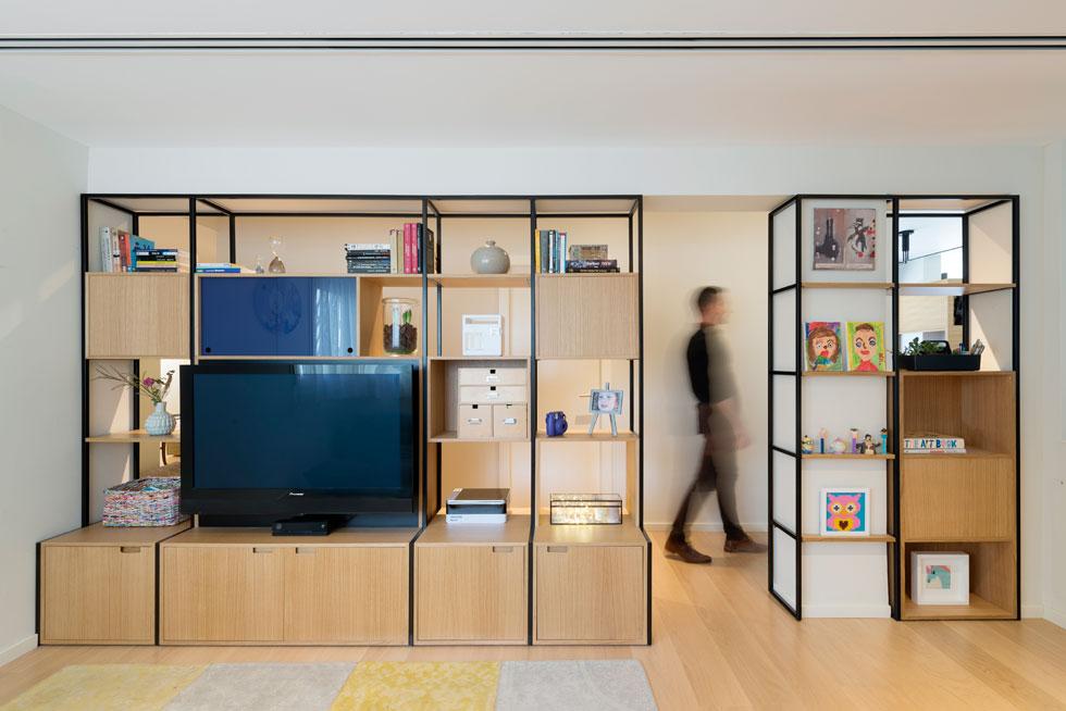 מבט מחדר המשפחה, שנמצא באמצע הדירה, אל המסדרון. הקיר הורד ובמקומו נבנתה ספרייה ממסגרות ברזל שחורות וקוביות עץ. הרהיט שימושי משני צידיו, ואווריריותו מחברת בין חלקי הדירה השונים (צילום: גדעון לוין)