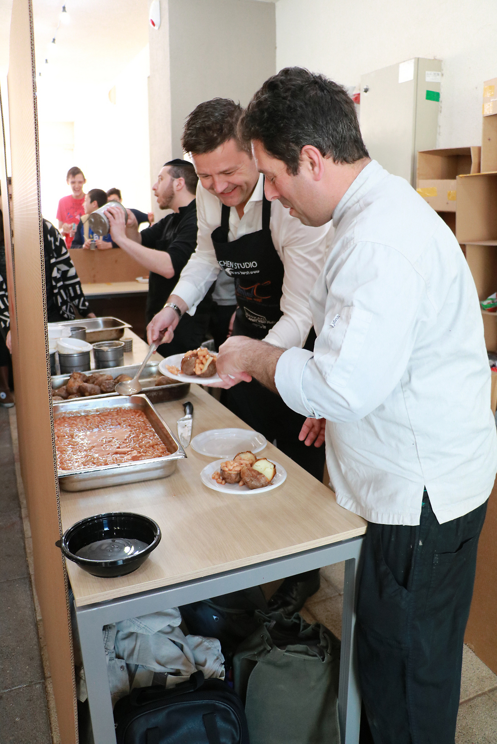 Deputy British Ambassador Tony Kay, left, helps Chef Itai Farkas in the kitchen (Photo: Amnon Hass)