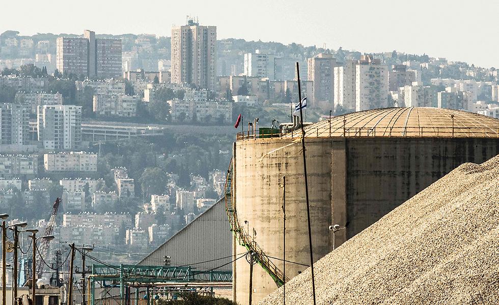 """""""בחברה נאחזים בקרנות המזבח"""". מכל האמוניה על רקע בתי האזור (צילום: AFP)"""