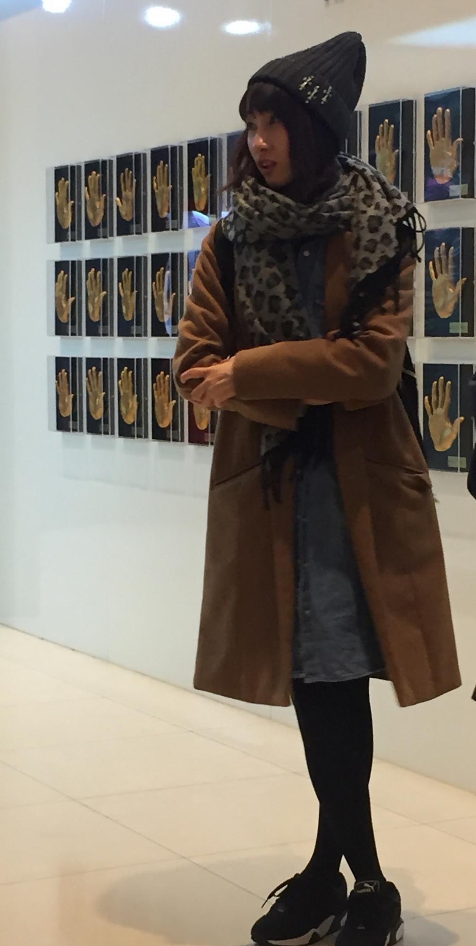 מעריצה לצד קיר טביעות האצבע של כוכבי הפופ הקוריאני