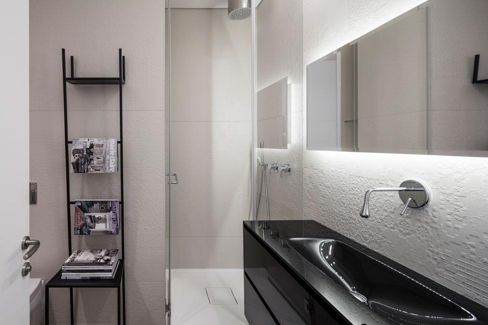 בחדר הרחצה של האורחים ארון כיור עשוי זכוכית שחורה, שהובא בשלמותו מאיטליה. גם האריחים דמויי התחרה הם בעיצוב פטריסיה אורקיולה (צילום: עמית גרון)