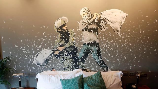 ישראלי ופלסטיני במלחמת כריות מעל המיטה. הציור בחדר מס' 3 (צילום: AFP) (צילום: AFP)
