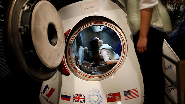 woman wearing a prototype of Stemrad's new protective vest, Astrorad, sits inside Russian spacecraft, Excalibur-Almaz Space Capsule (Photo: Reuters)