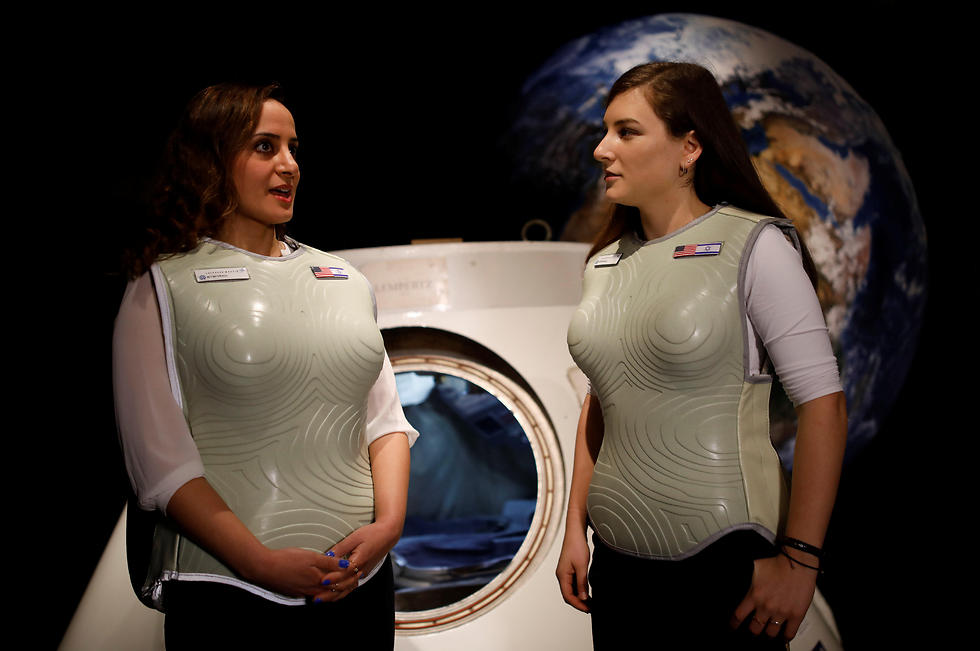 Women wearing prototypes of Stemrad's new protective vest, Astrorad, stand near Russian spacecraft, Excalibur-Almaz Space Capsule (Photo: Reuters)