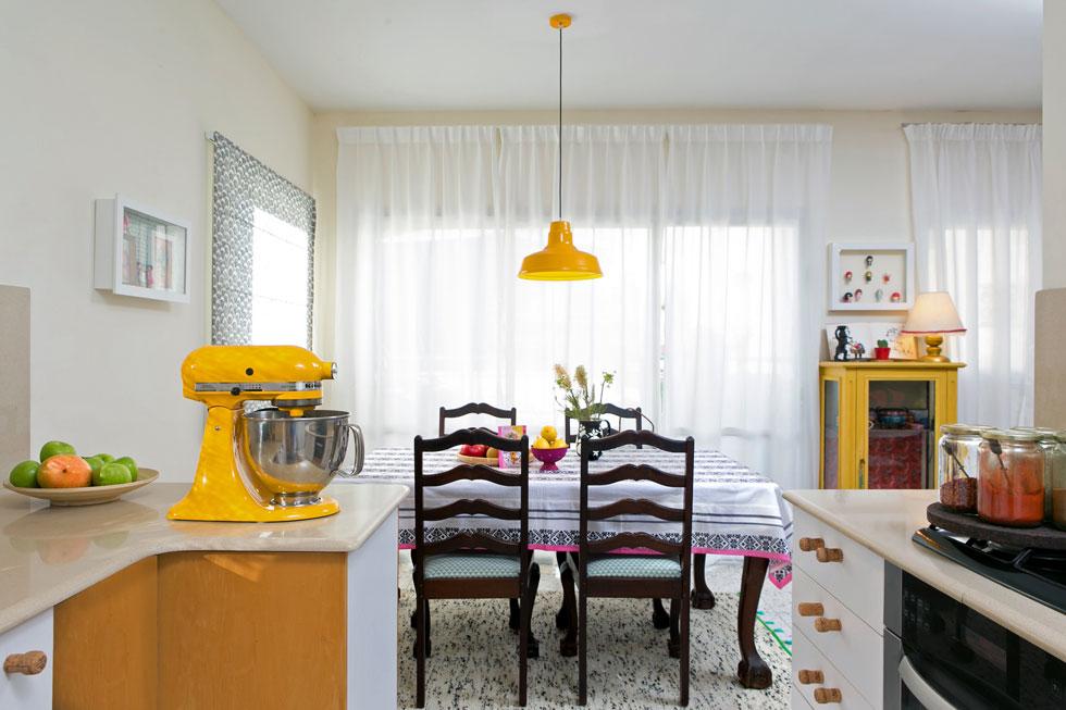 אגמון רצתה להחליף את שולחן האוכל הישן והכיסאות הכבדים סביבו, אך בן זוגה התעקש עליהם. לכן טיפלה בהם בעזרת טקסטיל וצבע: את הכיסאות רפדה מחדש בעצמה, תחת השולחן פרשה שטיח קליל ואת פניו כיסתה במפה. מנורה צבעונית משלימה את הצבעים מעל (צילום: שירן כרמל)