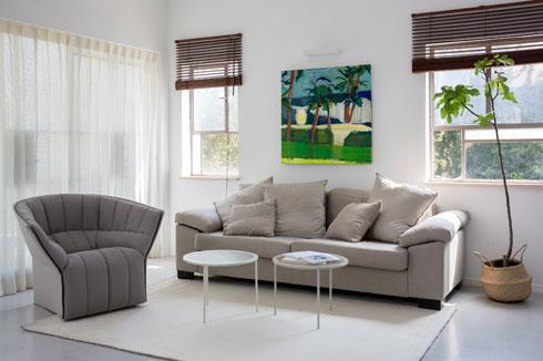 פינת הסלון. על הקיר ציור של מאיר סידי. הווילון  על וויטרינת היציאה למרפסת יובא מיפן. הוא עשוי נייר ארוג  ומחדיר לחדר אור רך (צילום: שי אפשטיין)