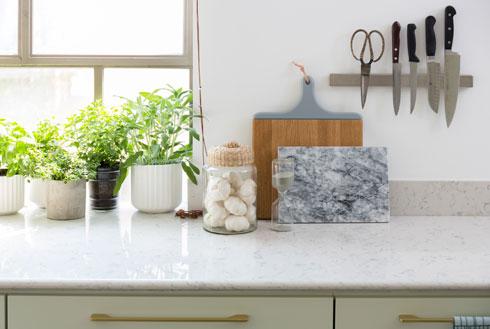 משטח העבודה במטבח עשוי שיש לבן מגויד באפור בהיר. הארונות צבועים בירוק אפרפר, והידיות שלהם מפליז (צילום: שי אפשטיין)