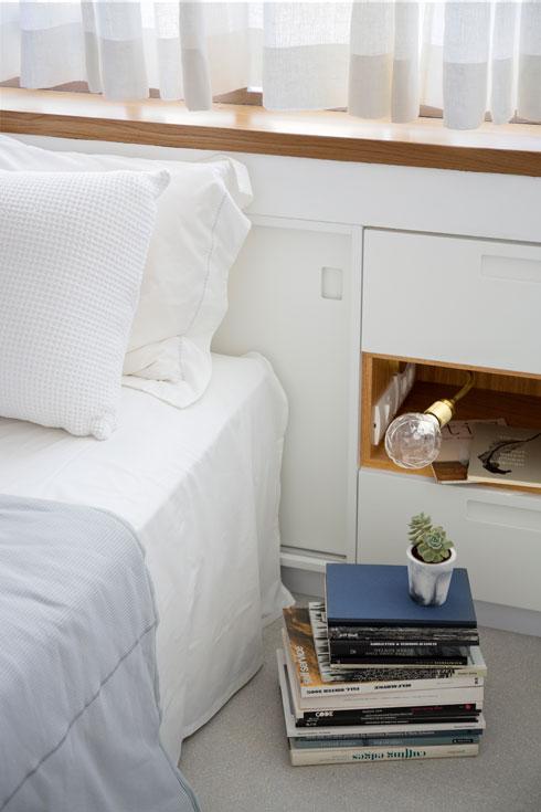 המיטה בחדר השינה נשענת על נישה קיימת שהפכה לארון. מנורת הלילה מציצה ממגרעת בארון  (צילום: שי אפשטיין)