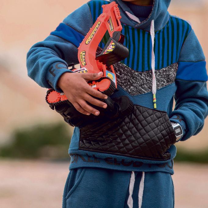 """אחד מילדי אום אל־חיראן אוחז את טרקטור הצעצוע שקיבל מילדי לקייה. """"יש לו את כל ההזדמנויות שבעולם"""""""