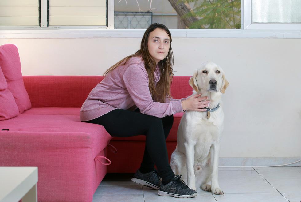 """שביט חזן בביתה שבחולון עם הכלב הומר. """"כשאני יוצרת קשר עין עם בן אדם, הוא שוכח שאני לא רואה, וזה כבר לא מפריע לו"""" (צילום: דנה קופל)"""