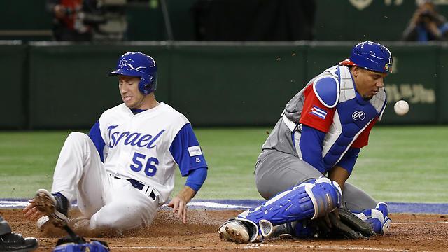Israel's Ty Kelly scores past Cuba's catcher Yosvani Alarcon in the sixth inning (Photo: AP)
