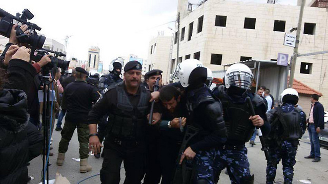 Palestinian police disperse the crowd