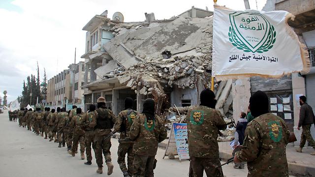 """מדינה שנשלטת על ידי המשטר, המורדים ודאעש. לוחמי ארגון """"ג'ייש אל-פתח"""" צועדים באידליב (צילום: AFP)"""