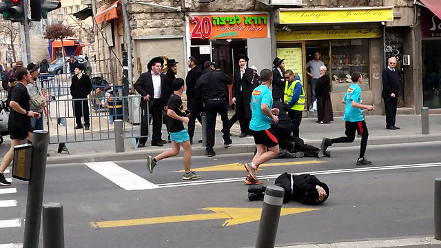 Runners skipping over the protestor (Photo: Amitai Sedes)