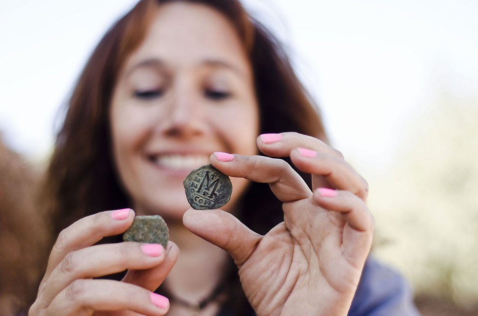 Annette Landes-Nager, excavation director on behalf of the Israel Antiquities Authority, with one of the coins. (Photo: Yoli Shwartz, courtesy of the Israel Antiquities Authority)